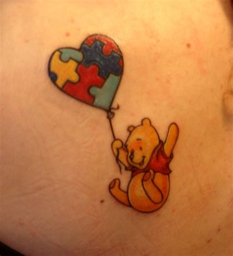 a super cute tattoo of winnie the pooh flying with the