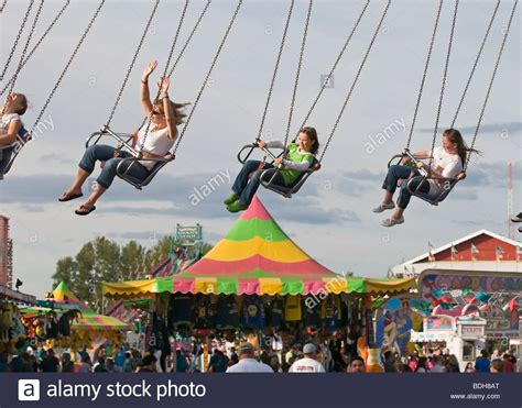 swings at the fair people at the county fair fly high in a chain swing ride
