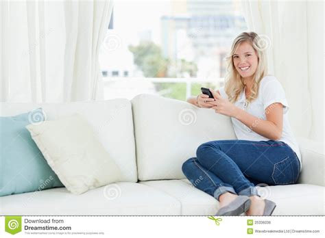 woman couch a woman sitting sideways on the couch as she uses her