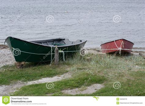 small fishing boats canada red and green fishing boats tied off with rope stock photo