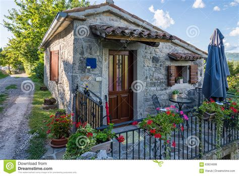 small stone house with a metal fence stock photo image