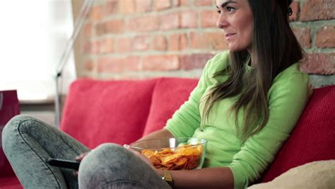 woman eats couch young woman eating chips and watching tv on sofa stock