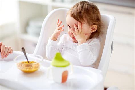 baby zu hause baby das im highchair sitzt und zu hause isst stockbild