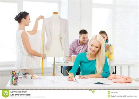 dress design education smiling fashion designers working in office stock photo