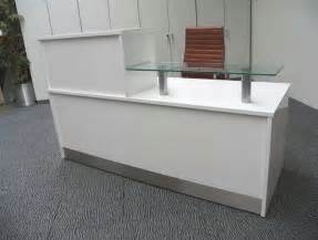 Grey carpet with small ikea reception desk with brown leather swivel