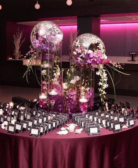 Glass cylinder decorations overflowing with exotic flowers