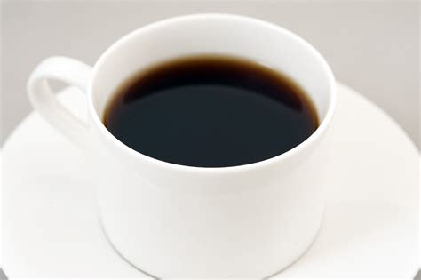 black energizing coffee served   white cup  stock