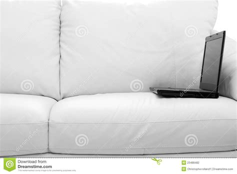 laptop on couch black laptop computer on white sofa stock photography