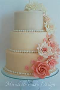 3 tier wedding cake in shades of pink with cascading roses