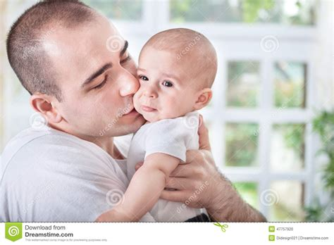 comforting a crying baby gentle young father comforting crying baby stock photo