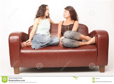 sit on the couch young women sitting on sofa and talking stock photography