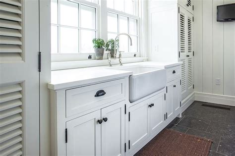 white cabinets with rubbed bronze hardware cottage laundry room features white shaker cabinets