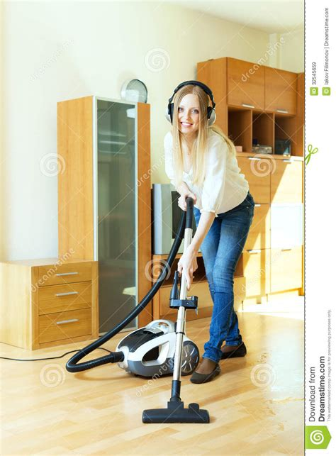 Vacuum Cleaner Happy King happy haired in headphones cleaning with vacuum clean royalty free stock images
