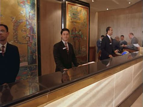 hotel front desk clerk dolly to portrait hotel desk clerk standing