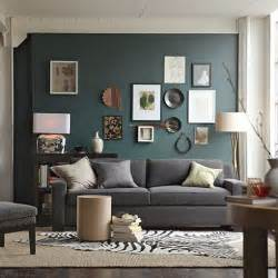 Dark teal colored accent wall in living room with grey couch