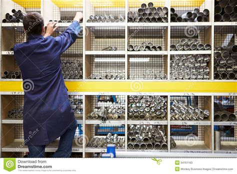 apprentice checking stock levels in store room stock
