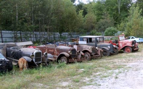 field full of prewar cars in maine