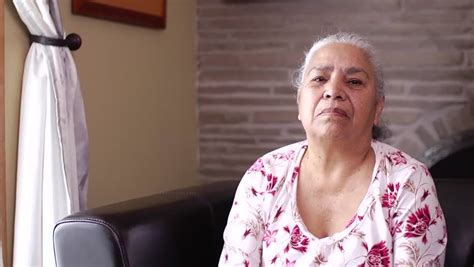 wigs for 80 year old hispanic women a latin woman senior citizen inserts her hearing aid and
