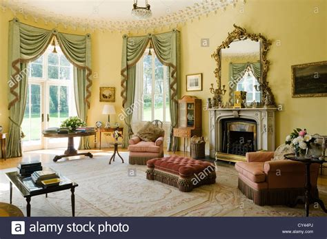 gilt room pale green fringed curtains in yellow drawing room with gilt framed stock photo royalty free