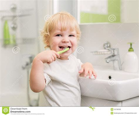 kid in bathroom happy kid brushing teeth in bathroom stock photo image