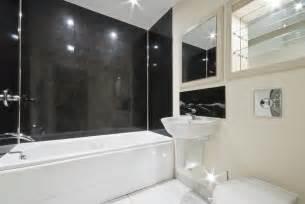 Sleek and simple modern bath design uses large black granite tiles