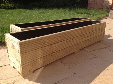 large wooden garden planter trough in decking boards
