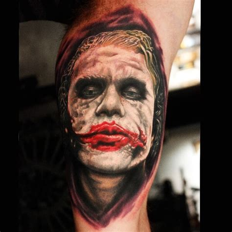 joker tattoo on biceps realism style colored biceps tattoo of evil joker