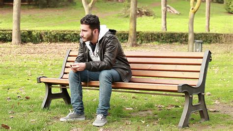 sitting on a park bench song a guy sits on a bench at park and wearing headphones to