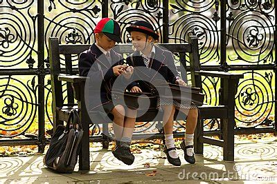 sister company of bench brother and sister eating on wooden bench stock photo