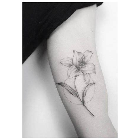 small lily tattoos line on the left inner arm artist