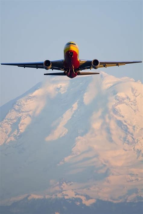dhl b767 281 freighter climbs out from seattle boeing field in front of mount rainier cargo