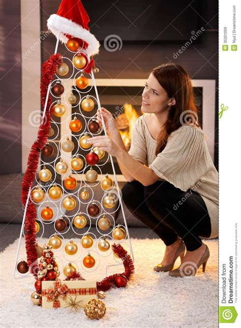 pretty woman decorating modern christmas tree stock image