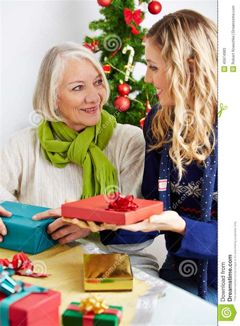 woman giving senior gift for christmas stock photo image