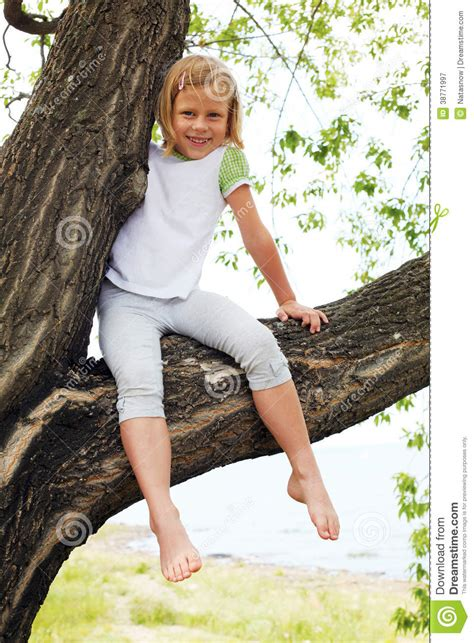 little legs cute girl sitting on a tree in summer stock image image