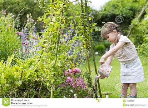 girl watering flowers cute little girl watering flowers in garden stock image
