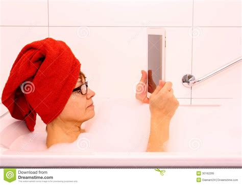 mature bathtub mature woman in bathtub with tablet computer royalty free