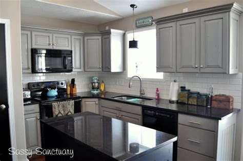 gray painted kitchen cabinets with black appliances