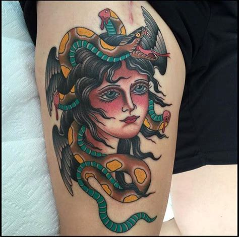 black medusa face tattoo on upper back by anto
