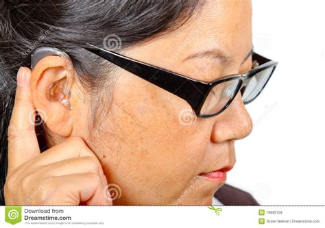 hairstyle for people who wear hearing aids woman with eyeglasses wearing hearing aid stock image