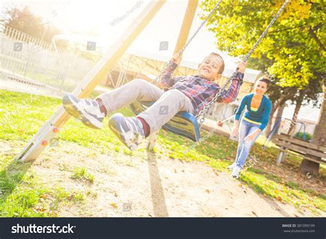 is swinging fun young boy having fun on the swing his mother or