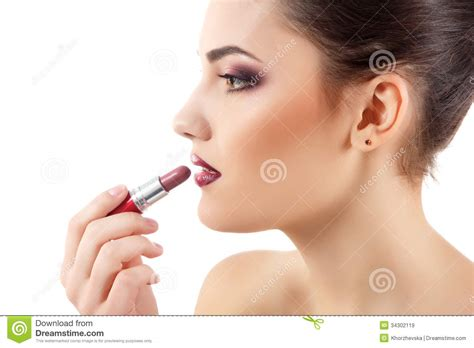 portrait of teenage girl putting lipstick on while looking at her beauty portrait of young beautiful woman puts on lipstick
