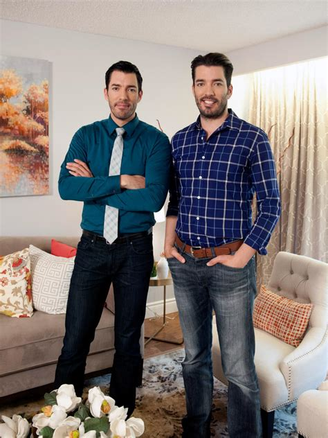 hgtv property brothers drew and scott pose in renovated living room hosts drew