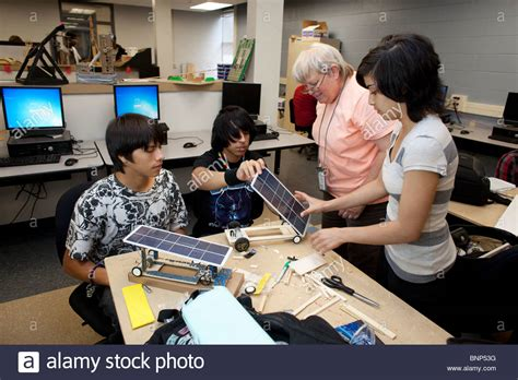 Background Check For Teachers Checks Students Work On Model Solar Car In Engineering Class Stock Photo
