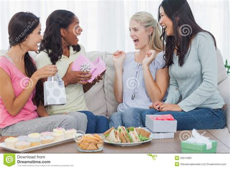 couch party friends offering gifts to woman during party stock image