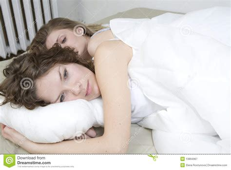 cuddling in bed sisters cuddling in bed royalty free stock photography