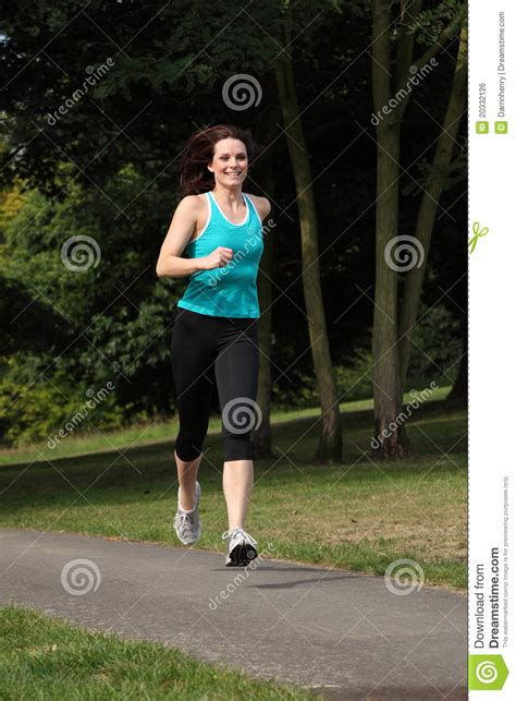 beautiful fit young woman running   park stock photo