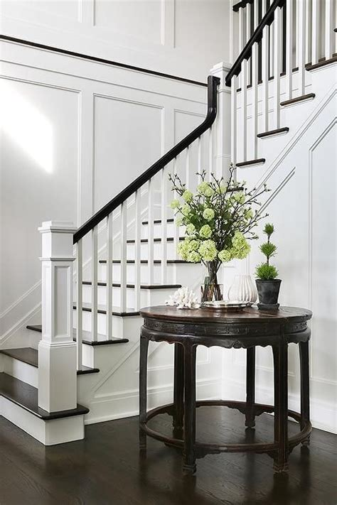 black banister white spindles chic foyer opens to a staircase fitted with white spindles
