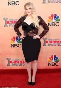 Meghan trainor in form fitting dress as she attends iheart music