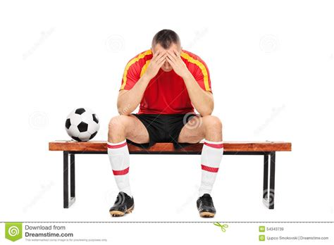 football player on bench worried young football player sitting on a bench stock