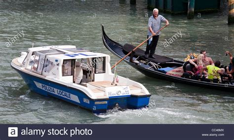 gondola and boat canal scene with gondola and police boat in venice italy